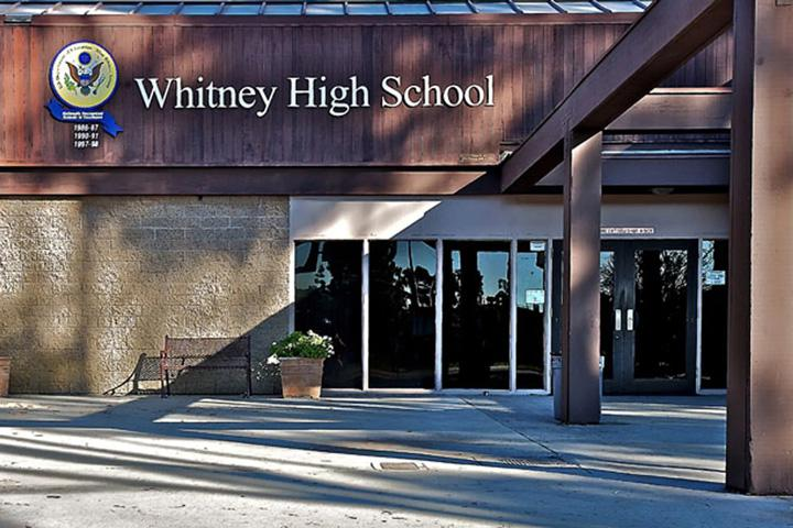 Entrance to Whitney High School with school name logo columns sliding glass doors bench and planter