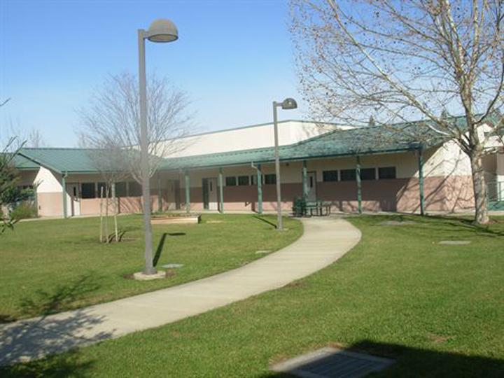 Victory High School campus with light poles green lawn concrete walkway and main building