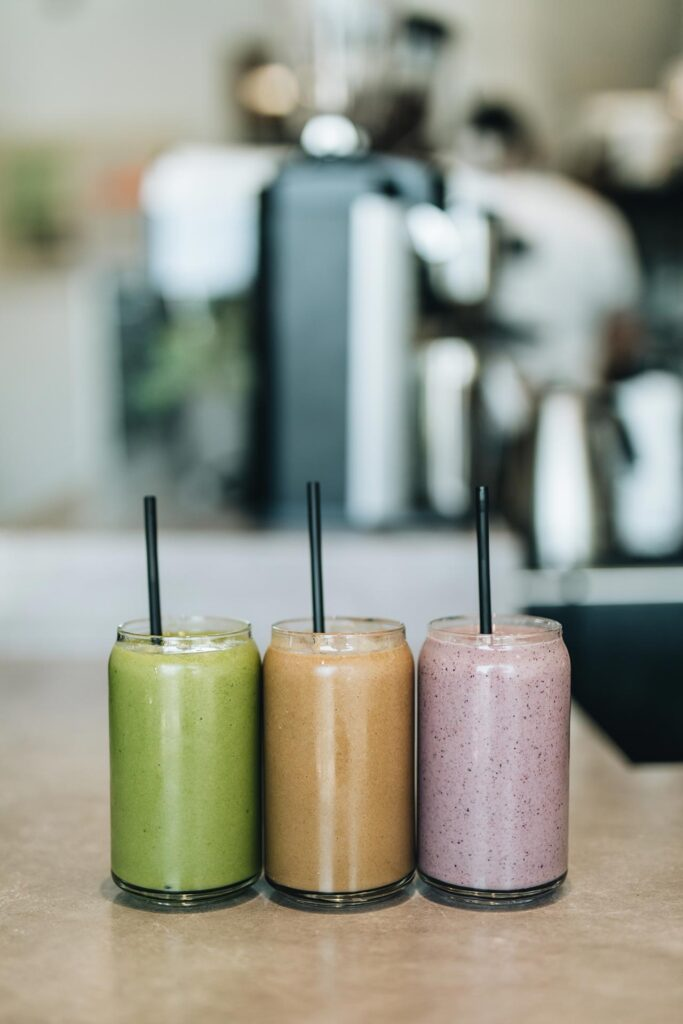 One green orange and purple smoothie in glasses with black straws in a line on a countertop