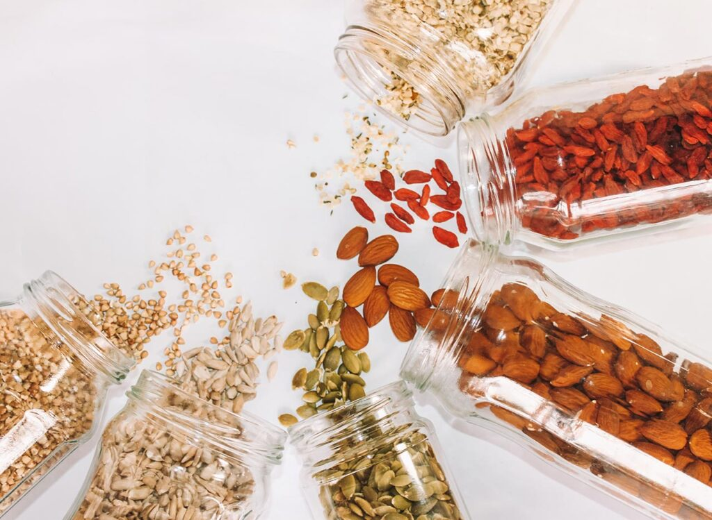 Spilled glass containers of nuts dried fruits and seeds on a white background