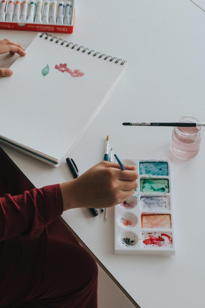 a person wearing red clothing is painting a leaf and flowers on a white sketchbook with a blue-green purple orange and red watercolor paint kit that is resting on a white table