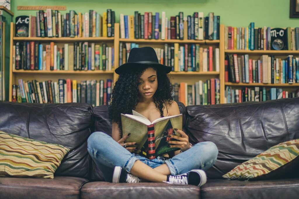 young brown skin woman with black hair a black hat blue jeans and black converse sitting on a couch with bookshelves in the background and reading the novel water for elephants