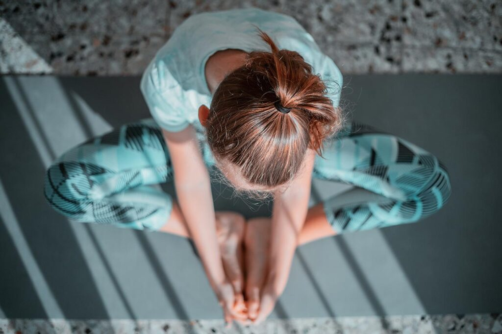 young caucasian woman with auburn hair in workout clothes and a ponytail doing a yoga butterfly position while on a yoga mat