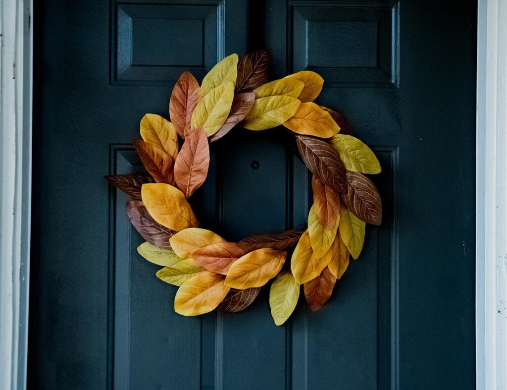 wreath made from yellow red orange and brown leaves hanging on a blue wooden door